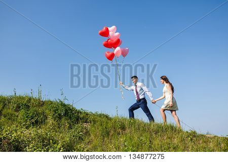 Happy wedding couple walking with red air-balloons