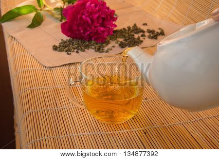 Pouring green tea from a white ceramic teapot in glass Cup.