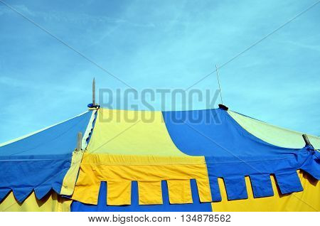 top of a colorful medieval tent with blue sky