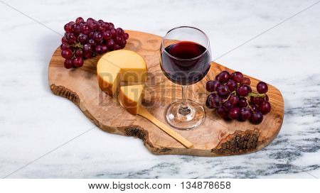 Overhead view of red wine cheese and grapes on wooden server with marble counter underneath. Selective focus on top of wine glass.