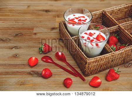 Two Glasses of Yoghurt,Red Fresh Strawberries in the Rattan Box with Plastic Spoons on the Wooden Table.Breakfast Organic Healthy Tasty Food.Cooking Vitamins Ingredients.Summer Fruits.
