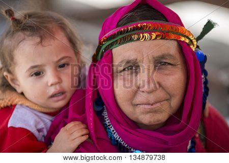 AYDIN, TURKEY - APRIL 4, 2016: Woman carrying her baby on her back in the city of Aydin, in Turkey.