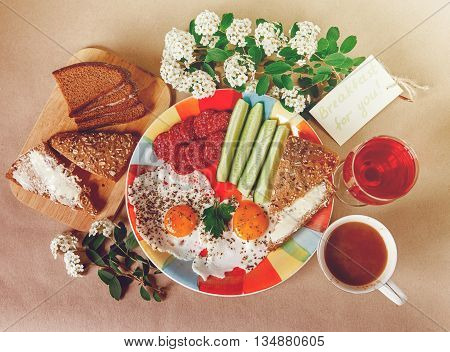 Delicious Tasty Breakfast from Eggs,Bread with Butter,Sausage on the Colorfull Plate.CoffeeRed Juice with White Flowers.Wish Card.Brown Background.Top View