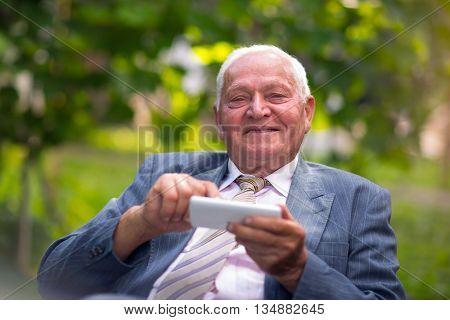 Senior man on mobile smart phone outdoor