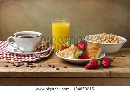 Breakfast setting with coffee and orange juice on wooden table