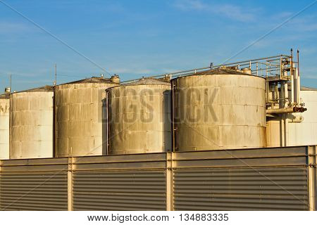 Large industrial wine vats of the factory over blue sky