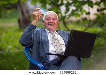 Senior man holding credit card outdoors laughing using the laptop