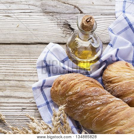Golden fragrant twisted baguettes on a simple wooden background on a white towel in hlopkovoi blue cage with olive oil and honeycombs. The concept of simple rustic healthy homemade food. selective focus