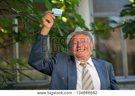 Old man holding credit card outdoors laughing