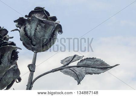 Metalworks art - big metal rose on sky background