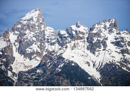 Beautiful sheer snow covered mountain peeks against blue sky crisp air natural scenic outdoor western landscape