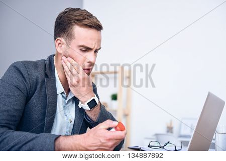Terrible toothache. Moody sick man sitting at the table and holding his jaw while going to tale pills