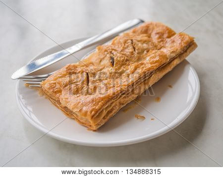 Tasty tuna patty on dish with knife and fork on the table