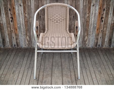 Metal chair with woven seat on old wooden floor background