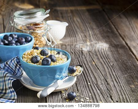 A pair of blue ceramic bowls full of breakfast cereal with fresh blueberries and milk. Selective focus. The concept of a healthy breakfast