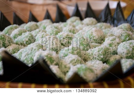 Indonesian traditional food called onde onde on plate with banana leaves accessories