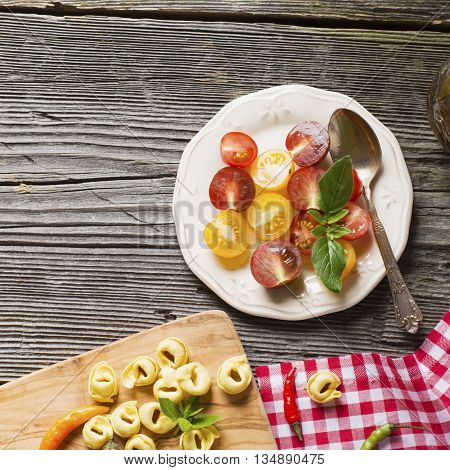 Healthy snack. White ceramic dish with a salad of multicolored cherry tomatoes with olive oil on a dark wooden background. Served for dinner with pasta tagliatelle on the board of the olive tree.
