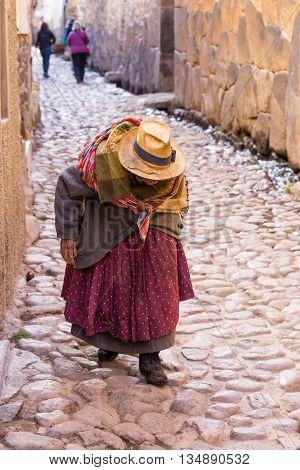 Unidentifiable Peruvian senior woman walking down cobblestone street