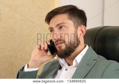 portrait of a successful business man with mobile phone in office