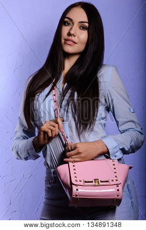 Charming brunette with long hair in denim clothes holding a pink handbag on a purple background