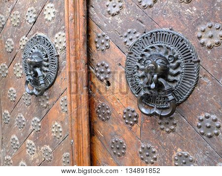 Old wooden door with iron lion knockers. Rustic vintage.