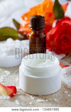 Face Cream With Roses, Bottle Of Aromatherapy Essential Oil And Salt On Brown Stone Background. Rose