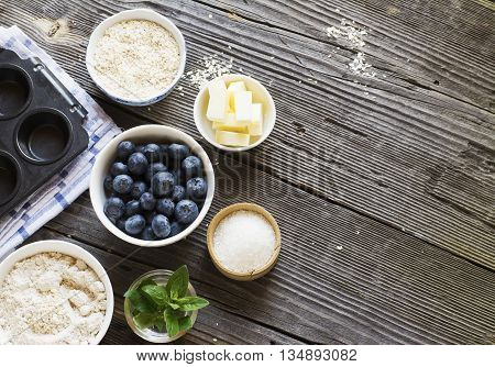 Healthy homemade cakes. Ingredients for blueberry muffins on a dark wooden background flour, sugar, butter, blueberry, blueberries, oatmeal
