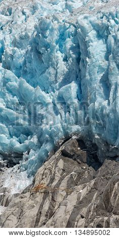 A towering glacier breaks over solid grey rock