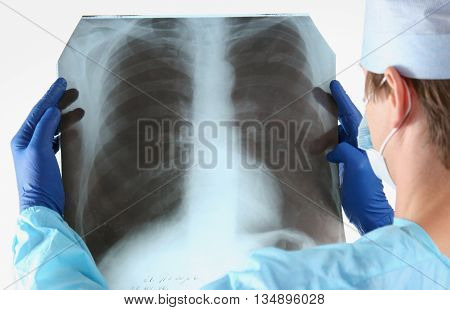 Doctor in blue uniform holding X-rays. clinic
