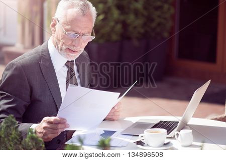 Like your work. Pleasant busy senior businessman sitting at the table and working with papers while using laptop
