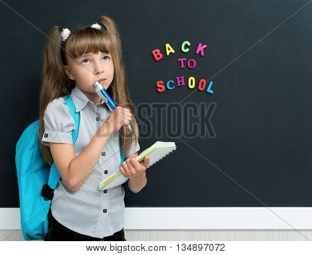 Back to school concept. Portrait of thoughtful schoolgirl with pen at the black chalkboard in classroom.