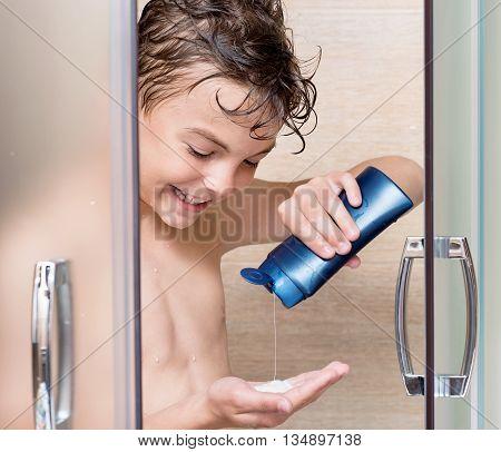 Happy boy washing head in shower in the bathroom