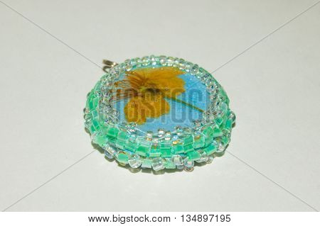 Small dried cherry blossom inside circle shaped pendant made of epoxy resin crystal and green beads close-up