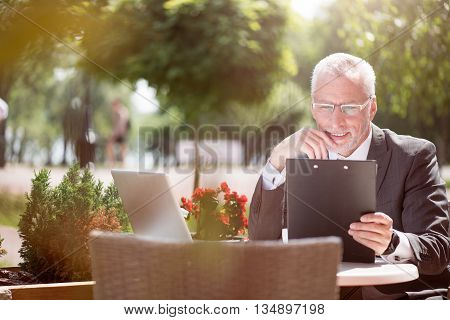 In a good mood. Positive smiling handsome senior man sitting at the table and holding folder while being involved in work