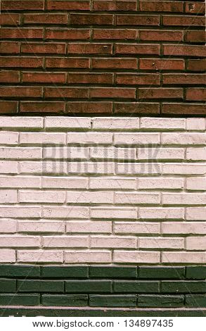 Three layer brick wall in earth colors, red earth, white, slate green.
