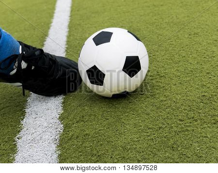 Soccer player kick the ball on football stadium field. Football or soccer concept