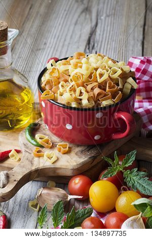 Homemade pasta. Traditional pasta in the form of hearts in a red ceramic pot before cooking surrounded by bright colored cherry tomatoes, hot peppers, oregano, with a jug of olive oil on the board of the olive tree.