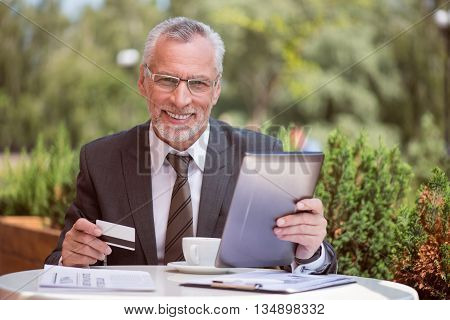 My everyday life. Pleasant cheerful handsome smiling senior man sitting at the table and using tablet while holding credit card