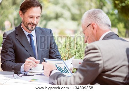 Raise your mood. Pleasant cheerful handsome man smiling and working while sitting with his colleague at the table outside