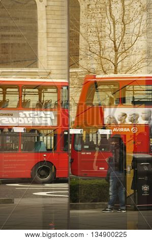 LONDON, UK - APRIL 01: The abstract reflections of tourists and red double-decker buses in the windows of an information center at the St. Paul's Cathedral on April 01, 2015 in London.