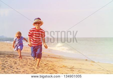 happy little boy and girl running on sand beach, family vacation