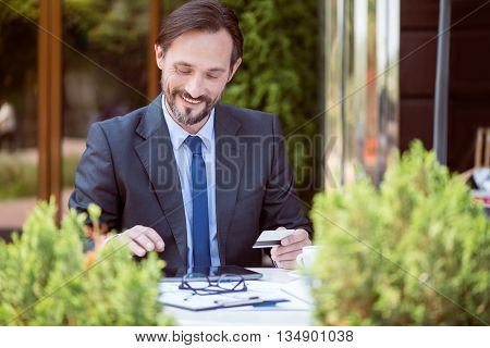 Convenient online banking. Positive delighted smiling and using tablet and holding credit card while sitting at the table