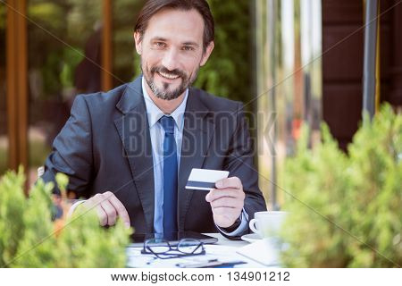 Contemporary user. Pleasant handsome smiling man sitting at the table and holding credit card while using tablet