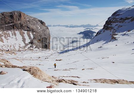 Hiker climbing the steep upper snow slopes of Mt.Pelmo, in the Dolomites