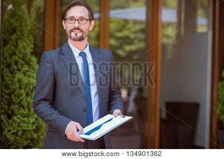 Confidence in mind. Pleasant delighted handsome man holding folder and looking aside while standing outdoor