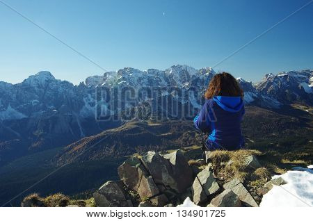 Looking at the Dolomites, sitting female hiker