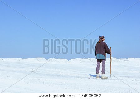 A man in his turban with a stick among the white desert under a clear blue sky - back view.