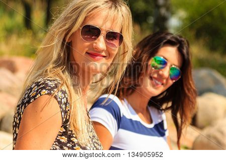 Happy women sun tanning and relaxing on beach. Joyful friends in sunglasses resting at sea. Summer relax and happiness.