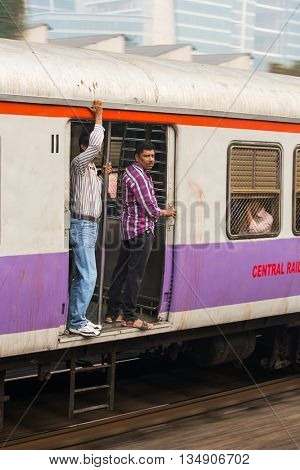 Mumbai, India - February 29, 2016: Unidentified men traveling via Suburban train in Mumbai, India.
