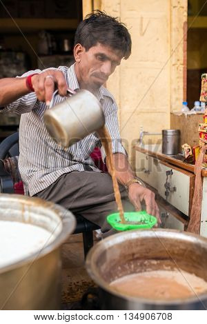 Jaisalmer, India - March 11, 2016 - Men pours cup hot milk tea Indian style or chai for customers in his shop along the street